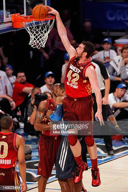 Kevin Love of the Minnesota Timberwolves and the Western Conference dunks against Dwight Howard of the Orlando Magic and the Eastern Conference...