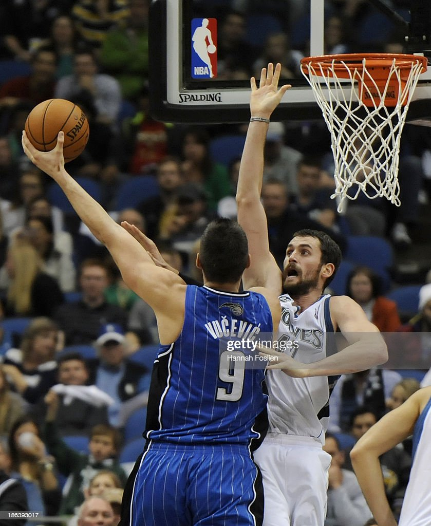 Kevin Love #42 of the Minnesota Timberwolves defends against a shot by Nikola Vucevic #9 of the Orlando Magic during the fourth quarter of the season opening game on October 30, 2013 at Target Center in Minneapolis, Minnesota. The Timberwolves defeated the Magic 120-115 in overtime.