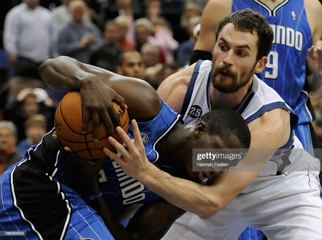 Kevin Love #42 of the Minnesota Timberwolves fouls Victor Oladipo #5 of the Orlando Magic during the fourth quarter of the season opening game on October 30, 2013 at Target Center in Minneapolis, Minnesota. The Timberwolves defeated the Magic 120-115 in overtime.