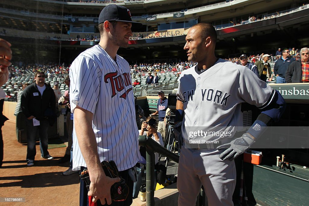 Kevin Love of the Minnesota Timberwolves greets Derek Jeter #2 of the New York Yankees after throwing out the ceremonial first pitch prior to the MLB game between the New York Yankees and the Minnesota Twins on September 26, 2012 at Target Field in Minneapolis, Minnesota.