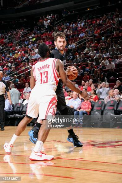 Kevin Love of the Minnesota Timberwolves handles the ball against James Harden of the Houston Rockets on March 20 2014 at the Toyota Center in...