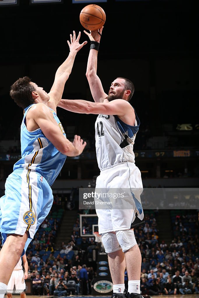 Kevin Love #42 of the Minnesota Timberwolves passes the ball over Danilo Gallinari #8 of the Denver Nuggets during the game between the Minnesota Timberwolves and the Denver Nuggets on November 21, 2012 at Target Center in Minneapolis, Minnesota.