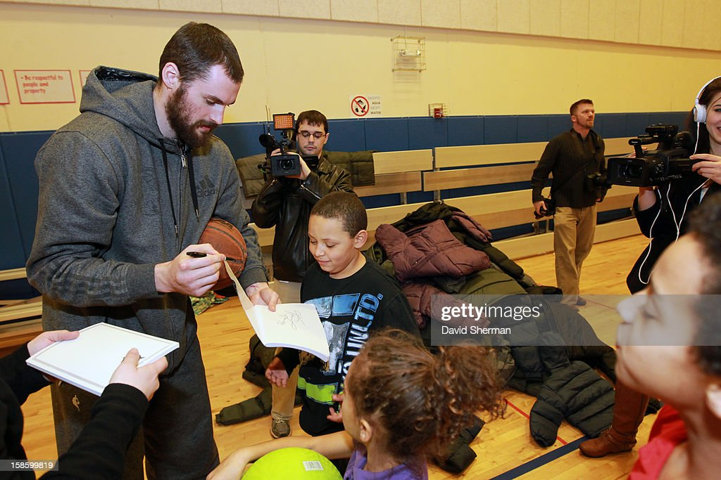 Kevin Love #42 of the Minnesota Timberwolves signs autographs for kids participating in the Salvation Army's After School Program after delivering coats collected during the fifth annual Kevin Love's Coat Drive to help those in need during the Holiday Season on December 19, 2012 at the Minneapolis Salvation Army Central Worship and Community Center in Minneapolis, Minnesota.