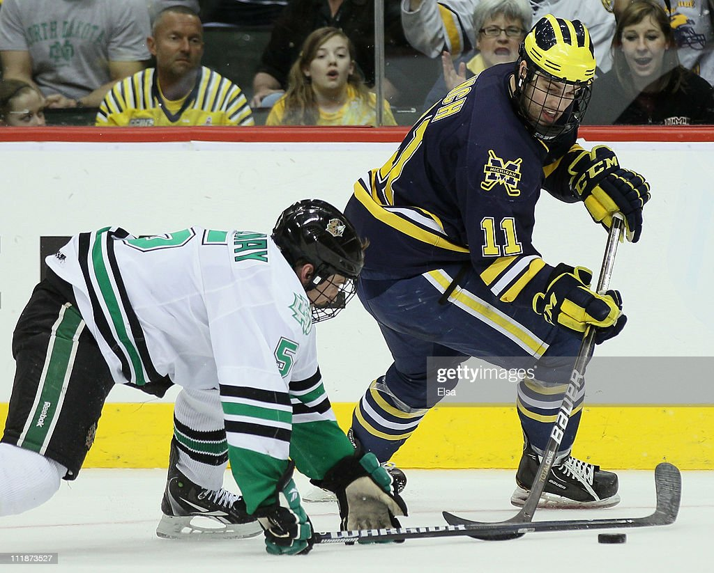 Kevin Lynch #11 of the Michigan Wolverines tries to get around Chay Genoway #5 of the North Dakota Fighting Sioux during semifinals of the 2011 NCAA Men's Frozen Four on April 7, 2011 at the Xcel Energy Center in St. Paul, Minnesota.