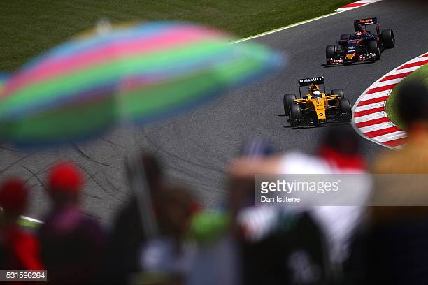 Kevin Magnussen of Denmark drives the 0 Renault Sport Formula One Team Renault RS16 Renault RE16 turbo ahead of Daniil Kvyat of Russia and Scuderia...