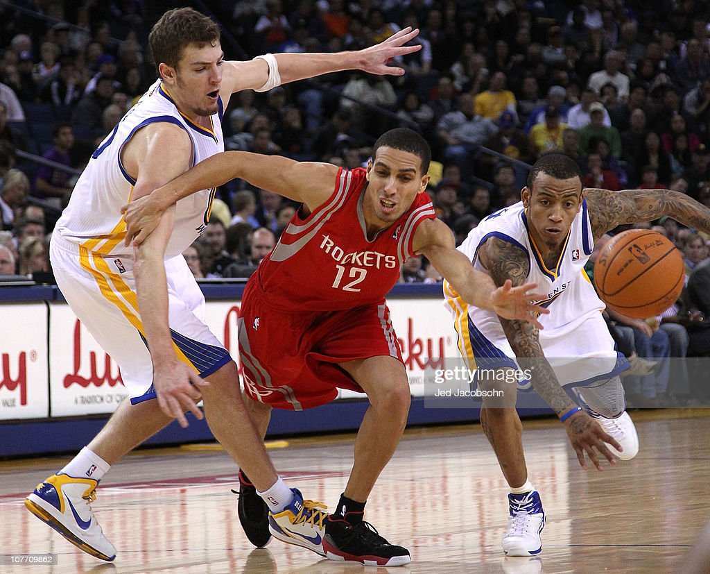 Kevin Martin of the Houston Rockets battles for the ball with David Lee and Monta Ellis of the Golden State Warriors during an NBA game at Oracle...
