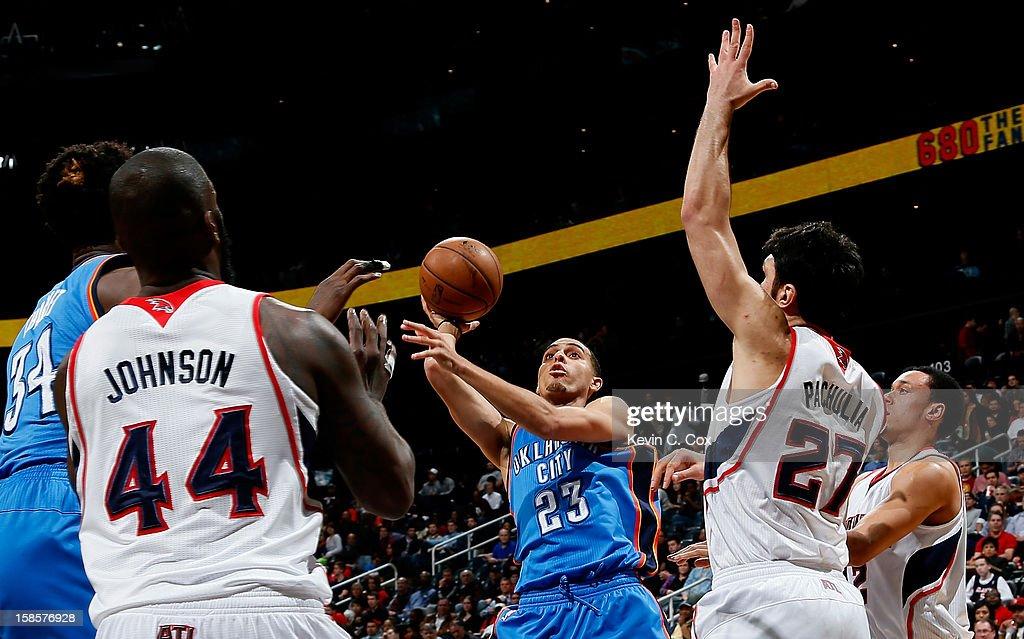 Kevin Martin #23 of the Oklahoma City Thunder shoots against Ivan Johnson #44 and Zaza Pachulia #27 of the Atlanta Hawks at Philips Arena on December 19, 2012 in Atlanta, Georgia.
