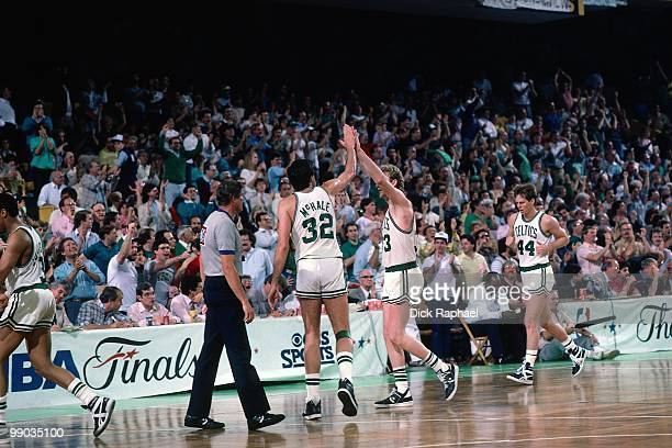 Kevin McHale and Larry Bird of the Boston Celtics high five each other during the 1986 NBA Finals at the Boston Garden in Boston Massachusetts The...
