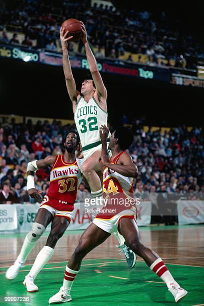 Kevin McHale of the Boston Celtics shoots takes the ball to the basket against Dan Roundfield and Mike Glenn of the Atlanta Hawks during a game...