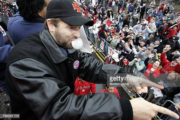Kevin Millar blows a bubble on Boylston Street while pointing to fans from a duck boat during a rolling rally parade to celebrate the Boston Red...