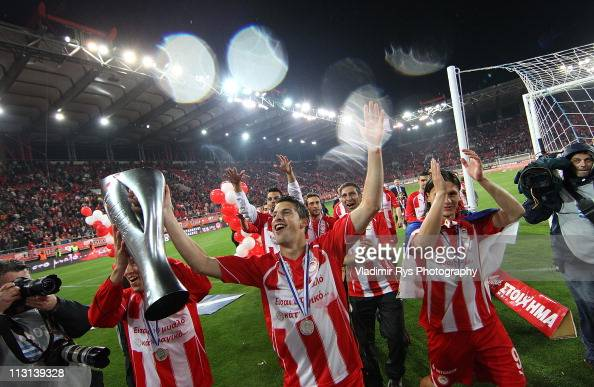 Kevin Mirallas and Marko Pantelic of Olympiacos celebrate with the championship trophy after finishing first in the league and claiming the club's...
