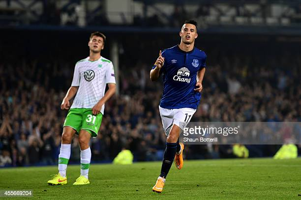 Kevin Mirallas of Everton celebrates after scoring his team's fourth goal whilst a dejected Robin Knoche of VfL Wolfsburg reacts during the UEFA...