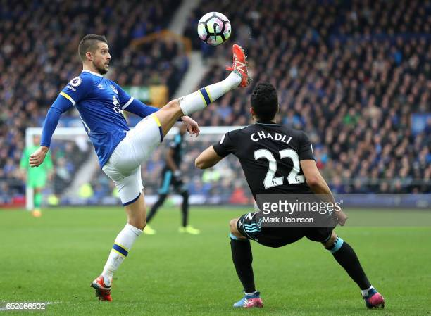Kevin Mirallas of Everton clears the ball while under pressure from Nacer Chadli of West Bromwich Albion during the Premier League match between...