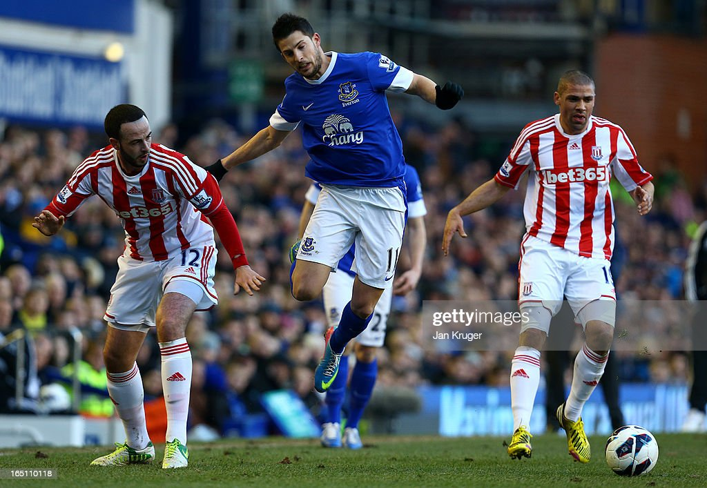 Kevin Mirallas of Everton loses his footing under pressure from Jonathan Walters and Marc Wilson of Stoke City during the Barclays Premier League match between Everton and Stoke City at Goodison Park on March 30, 2013 in Liverpool, England.