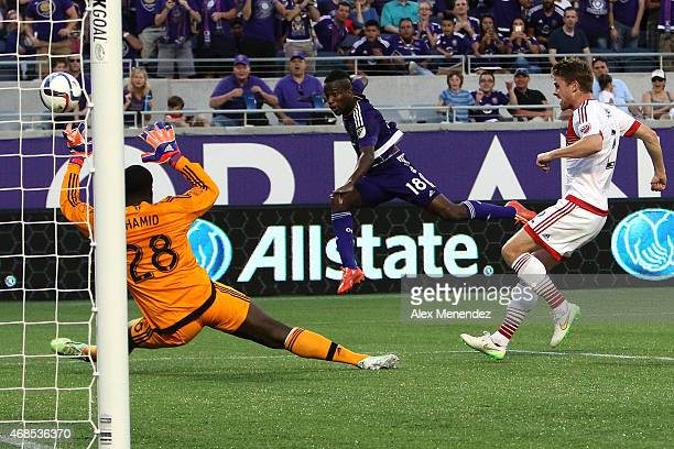 Kevin Molino of Orlando City SC shoots the ball as Bill Hamid of DC United attempts a save during a MLS soccer match at the Orlando Citrus Bowl on...