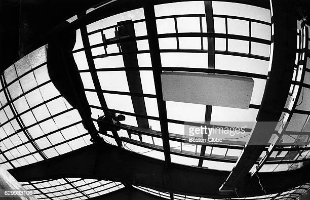 Kevin Montgomery adjusts his ladder while replacing the glass roof panels at the Isabella Stewart Gardner Museum in Boston August 1991