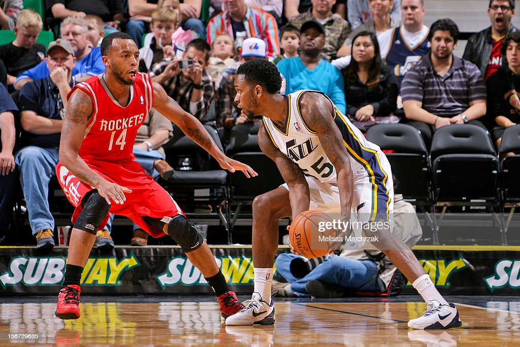 Kevin Murphy #55 of the Utah Jazz drives against <a gi-track='captionPersonalityLinkClicked' href=/galleries/search?phrase=Daequan+Cook&family=editorial&specificpeople=3847493 ng-click='$event.stopPropagation()'>Daequan Cook</a> #14 of the Houston Rockets at Energy Solutions Arena on November 19, 2012 in Salt Lake City, Utah.