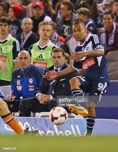 Kevin Muscat assistant coach and Ange Postecoglou head coach of the Victory look on as Archie Thompson of the Victory passes the ball during the...