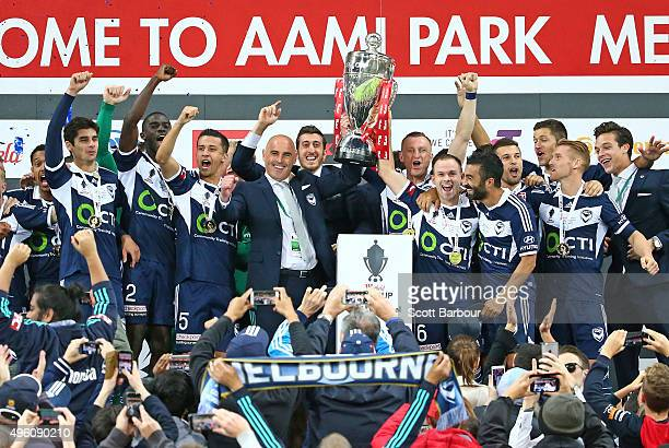 Kevin Muscat coach of the Victory and Victory players celebrate after being presented with the FFA Cup after winning the FFA Cup Final match between...
