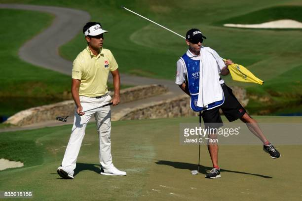 Kevin Na and his caddie react after missing an eagle putt on the 15th green during the third round of the Wyndham Championship at Sedgefield Country...