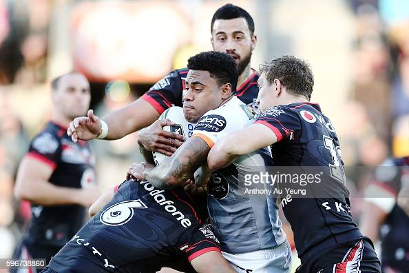 Kevin Naiqama of the Tigers is tackled by Thomas Leuluai and Ryan Hoffman of the Warriors during the round 25 NRL match between the New Zealand...