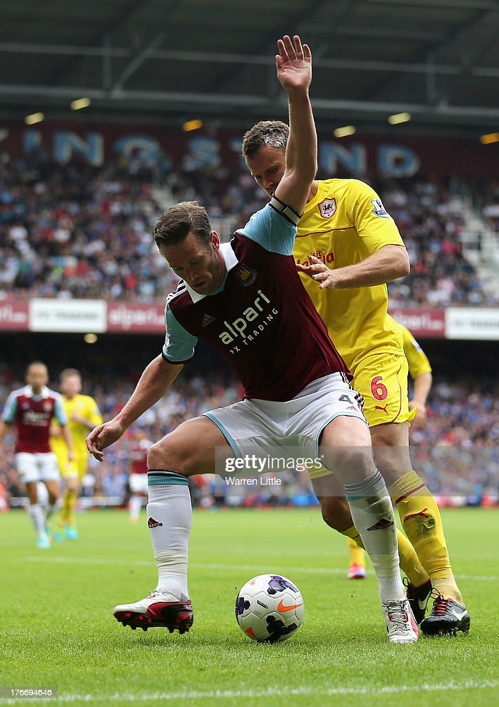 Kevin Nolan, Captain of West Ham is tackled by Ben Turner of Cardiff City during the Barclays Premier League match between West Ham United and Cardiff City at Boleyn Ground on August 17, 2013 in London, England.
