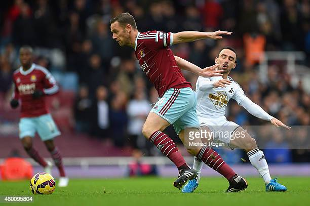 Kevin Nolan of West Ham and Leon Britton of Swansea City battle for the ball during the Barclays Premier League match between West Ham United and...