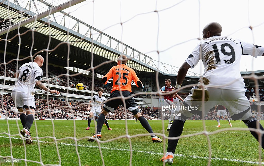 Kevin Nolan of West Ham United (2R) heads past Gerhard Tremmel (25) and Jonjo Shelvey of Swansea City (8) to score their second goal during the Barclays Premier League match between West Ham United and Swansea City at Boleyn Ground on February 1, 2014 in London, England.