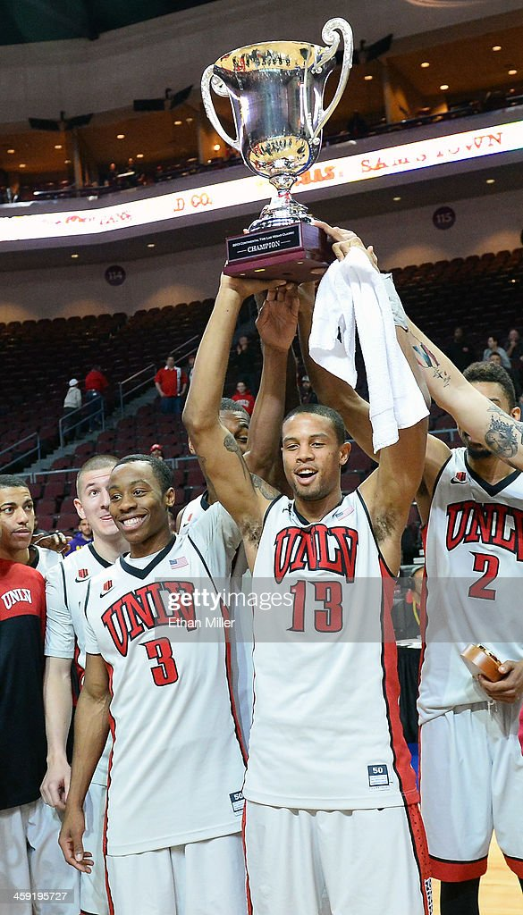 Kevin Olekaibe #3 and Bryce Dejean-Jones #13 of the UNLV Rebels celebrate with the championship trophy after defeating the Mississippi State Bulldogs 82-66 to win the 2013 Continental Tire Las Vegas Classic at the Orleans Arena on December 23, 2013 in Las Vegas, Nevada.