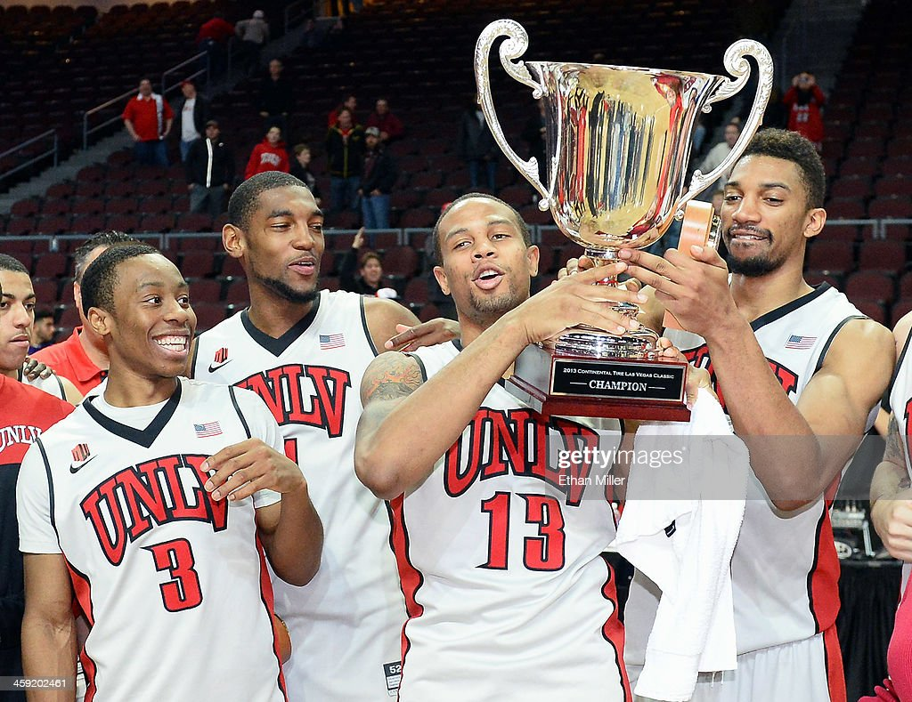 Kevin Olekaibe #3, Roscoe Smith #1, Bryce Dejean-Jones #13 and Khem Birch #2 of the UNLV Rebels celebrate with the championship trophy after defeating the Mississippi State Bulldogs 82-66 to win the 2013 Continental Tire Las Vegas Classic at the Orleans Arena on December 23, 2013 in Las Vegas, Nevada.
