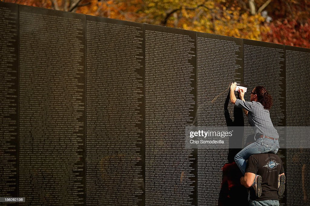 Kevin Palmer of Goshen, Connecticut, holds Michele Mathews on his shoulders as she makes a rubbing of where Palmer's uncle, Douglas Palmer's name is inscribed on the Vietnam Veterans Memorial the day after Veterans Day, November 12, 2012 in Washington, DC. Douglas Palmer died in 1966 while serving in the Navy in Vietnam.