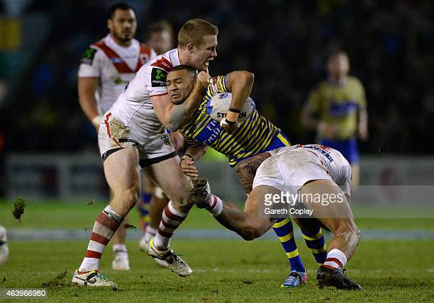 Kevin Penny of Warrington Wolves is tackled by Ben Creagh and Josh Dugan of St George Illawarra Dragons during the World Club Series match between...
