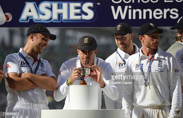 Kevin Pietersen of England takes a photo of the urn with Jonathan Trott Matt Prior and Ian Bell after England won the Ashes during day five of the...