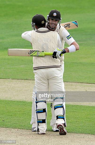 Kevin Pietersen of Surrey celebrates after he reaches his century with teammate Steven Davies during day three of the LV County Championship Division...