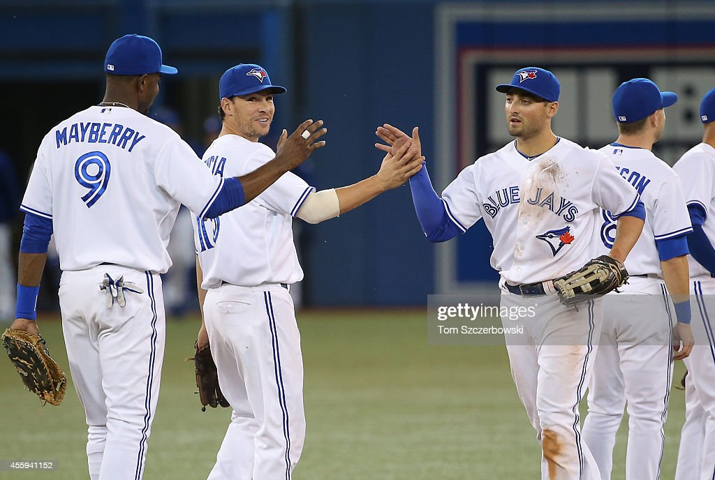 Kevin Pillar #11, Danny Valencia #15 and John Maybery Jr. #9 of the Toronto Blue Jays celebrate the win against the Seattle Mariners on September 22, 2014 at Rogers Centre in Toronto, Ontario, Canada.