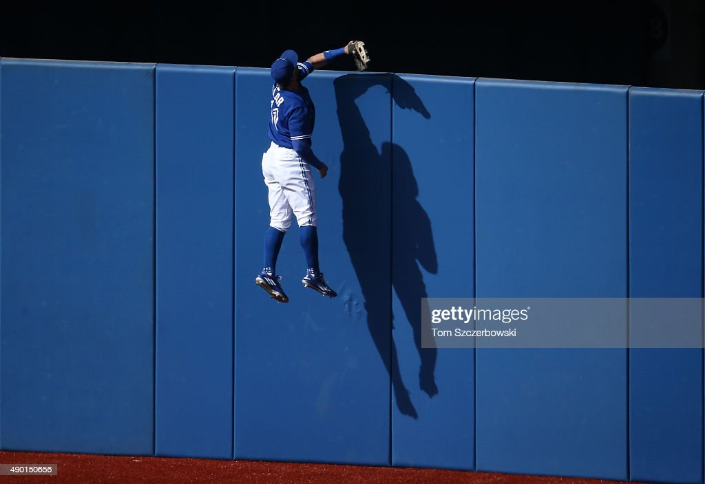 Kevin Pillar #11 of the Toronto Blue Jays climbs the wall but cannot get to a solo home run hit by Kevin Kiermaier #39 of the Tampa Bay Rays in the fourth inning during MLB game action on September 26, 2015 at Rogers Centre in Toronto, Ontario, Canada.