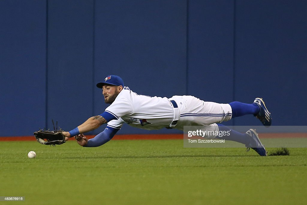 Kevin Pillar #11 of the Toronto Blue Jays dives but cannot get to an RBI double hit by Danny Valencia #26 of the Oakland Athletics in the first inning during MLB game action on August 11, 2015 at Rogers Centre in Toronto, Ontario, Canada.