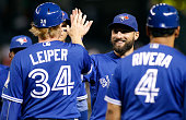 Kevin Pillar of the Toronto Blue Jays is congratulated by Tim Leiper and teammates after a 51 victory against the Arizona Diamondbacks during a MLB...