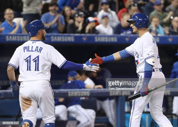 Kevin Pillar of the Toronto Blue Jays is congratulated by Troy Tulowitzki after scoring a run in the first inning during MLB game action against the...