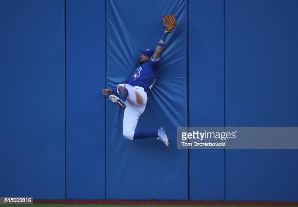 Kevin Pillar of the Toronto Blue Jays makes a leaping catch as he slams into the wall in the fifth inning during MLB game action against the Detroit...