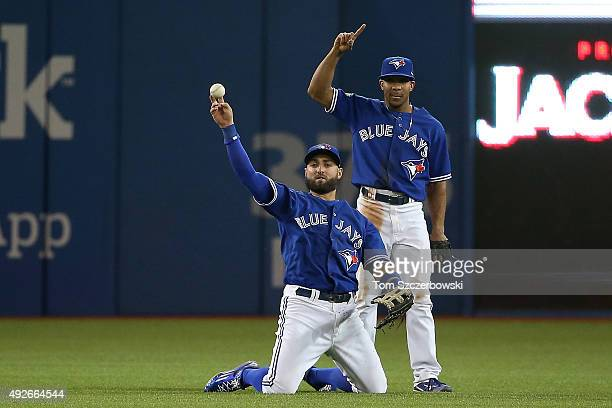 Kevin Pillar of the Toronto Blue Jays shows the ball in front of teammate Ben Revere after Pillar made a diving catch on a ball hit by Josh Hamilton...