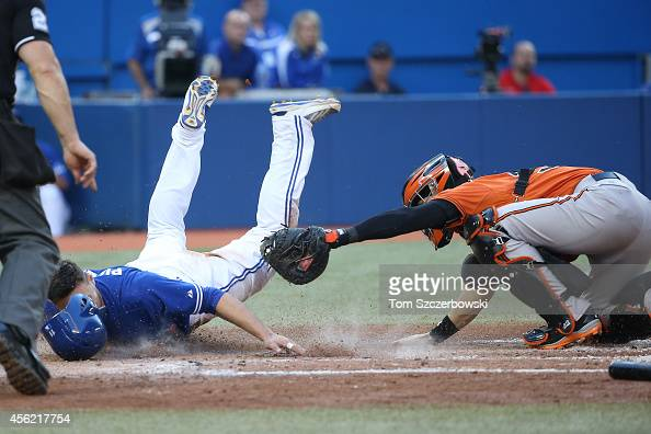 Kevin Pillar of the Toronto Blue Jays slides into home plate to score a run beating the tag in the seventh inning during MLB game action as Caleb...