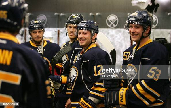 Kevin Porter and Mark Pysyk of the Buffalo Sabres enjoy a moment with teammates before a game against the Washington Capitals on March 30 2013 at the...