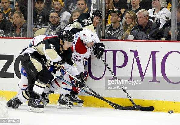 Kevin Porter and Patric Hornqvist of the Pittsburgh Penguins battle for a loose puck against David Desharnais of the Montreal Canadiens in the third...