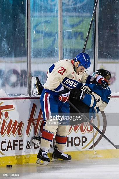 Kevin Porter of Rochester Americans puts Karl Stollery of Lake Erie Monsters into the boards during the third period on December 13 2013 at Frontier...