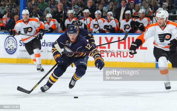 Kevin Porter of the Buffalo Sabres carries the puck up ice as Kent Huskins of the Philadelphia Flyers reaches in for the steal on April 13 2013 at...