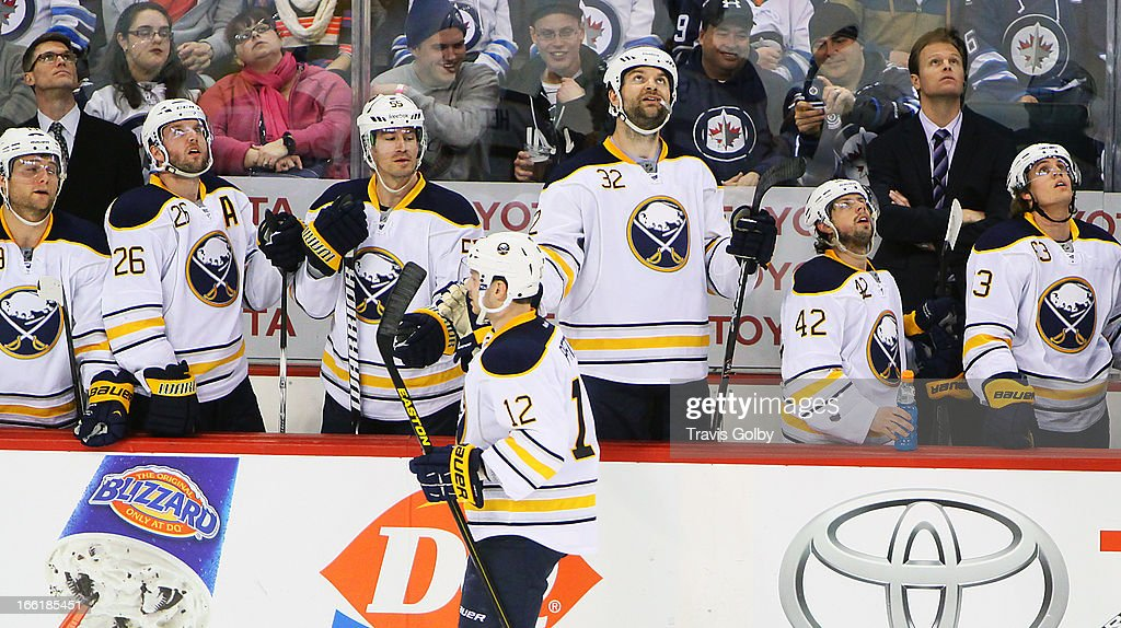 Kevin Porter #12 of the Buffalo Sabres is congratulated by teammates on the bench following his third-period goal against the Winnipeg Jets at the MTS Centre on April 9, 2013 in Winnipeg, Manitoba, Canada.