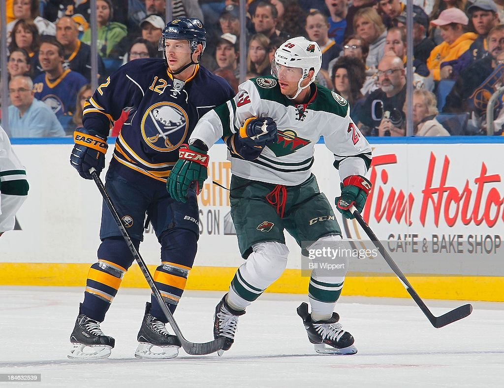 Kevin Porter #12 of the Buffalo Sabres, playing in his 200th NHL game, ties up Jason Pominville #29 of the Minnesota Wild on October 14, 2013 at the First Niagara Center in Buffalo, New York.