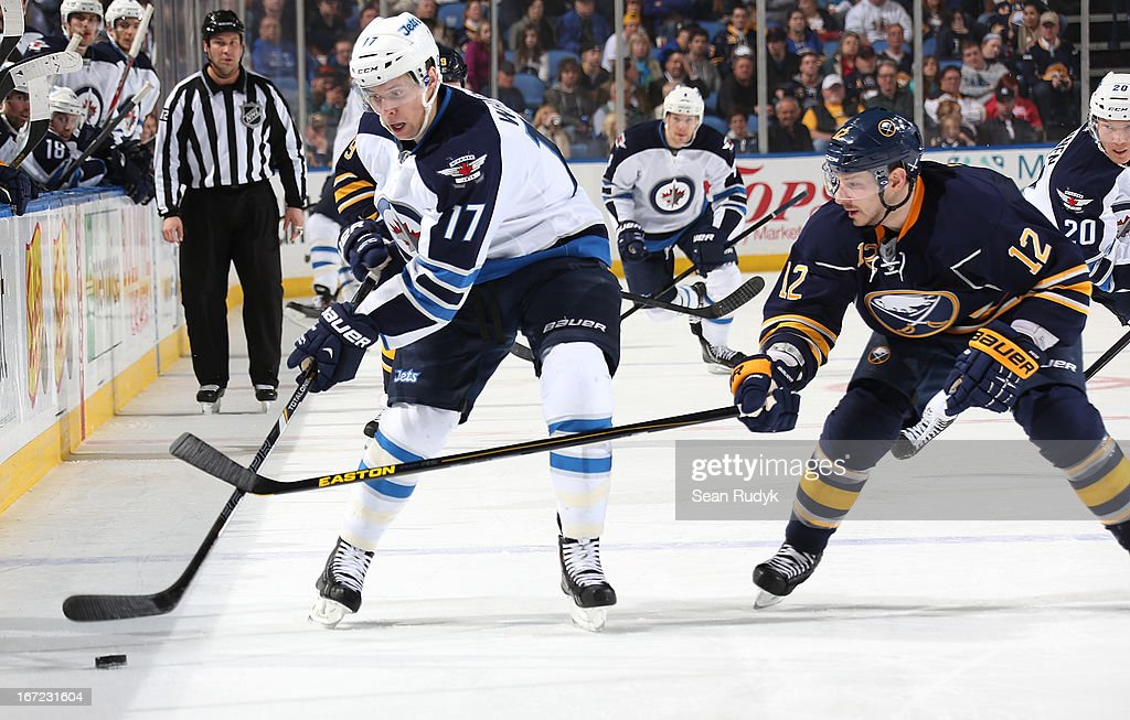 Kevin Porter #12 of the Buffalo Sabres reaches in to steal the puck from James Wright #17 of the Winnipeg Jets during the third period at First Niagara Center on April 22, 2013 in Buffalo, New York. Winnipeg defeated Buffalo, 2-1.