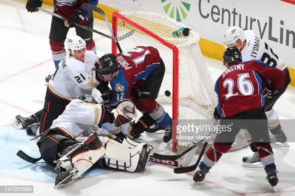Kevin Porter of the Colorado Avalanche is knocked into the net by Sheldon Brookbank and goaltender Jonas Hiller of the Anaheim Ducks at the Pepsi...
